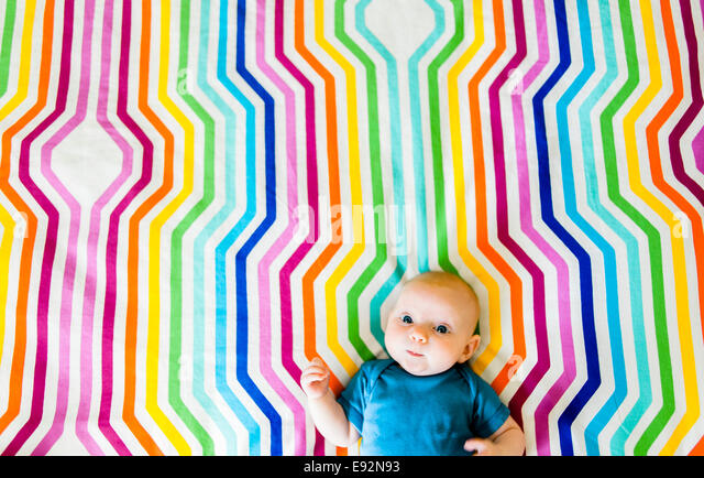 Baby Laying on Colorful Geometric Fabric, High Angle View - Stock Image