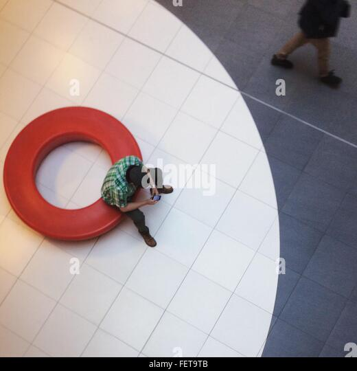 High Angle View Of Man Using Mobile Phone In Lobby - Stock Image