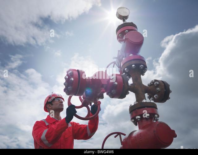 Worker turning valve on oil well - Stock-Bilder