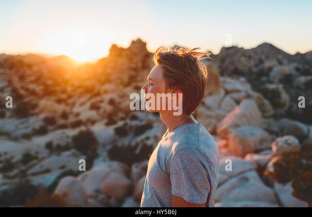 USA, California, Joshua Tree National Park, Young man contemplating at sunset - Stock Image
