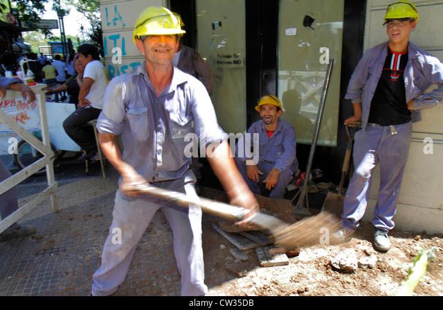 Argentina Buenos Aires Avenida Rivadavia sidewalk construction site Hispanic man worker laborer job hard hat safety - Stock Image