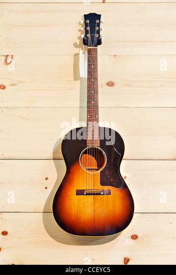 Acoustic guitar with label isolated on a wood grain wall - Stock Image
