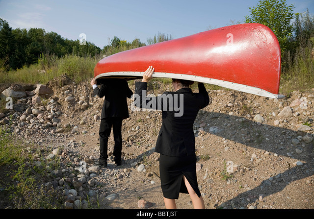 Business people carrying canoe - Stock Image