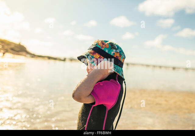 A child in a wetsuit and sunhat on a Cornish beach. - Stock Image