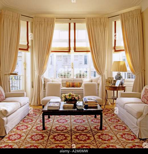Large living room with three sofas, patterned carpet and bay windows - Stock-Bilder