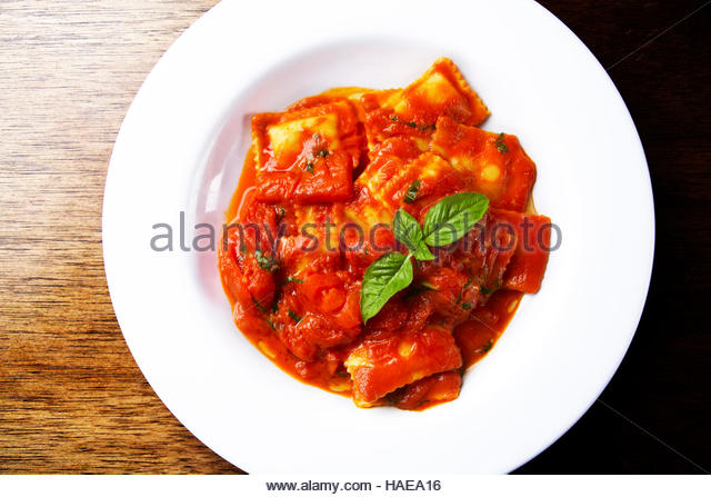 Four cheese raviolli with tomato sauce and basil - Stock Image