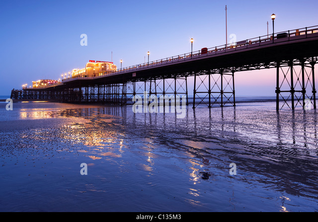 Worthing Pier illuminated at dusk - Stock-Bilder