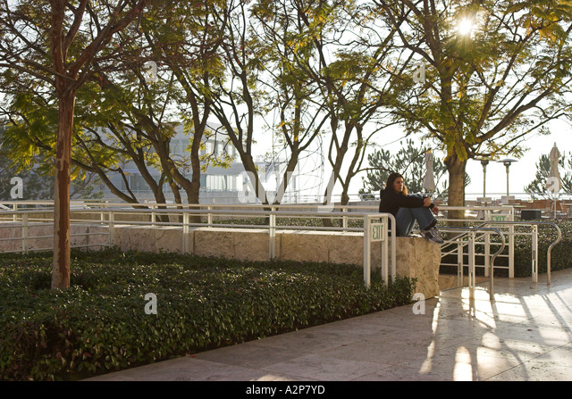 A young woman sits in the shade at the Getty Center. - Stock Image