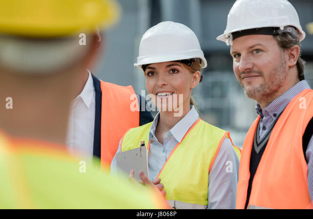 Smiling engineers meeting at construction site - Stock-Bilder