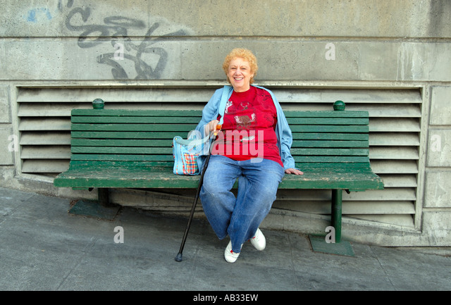 Woman with cane stops for a rest on a bench on a slanting street in Downtown Seattle, Washington. Stock Photo