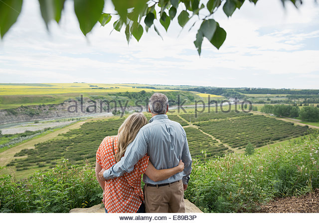 Hugging couple looking at view of countryside - Stock Image