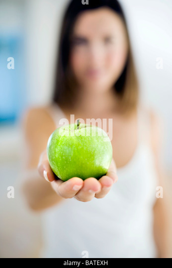 Apple held in a woman's hand. - Stock Image