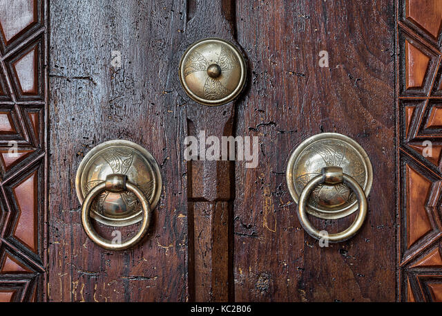 Closeup of two antique copper ornate door knockers over an aged wooden door, Suleymaniye Mosque, Istanbul, Turkey - Stock Image