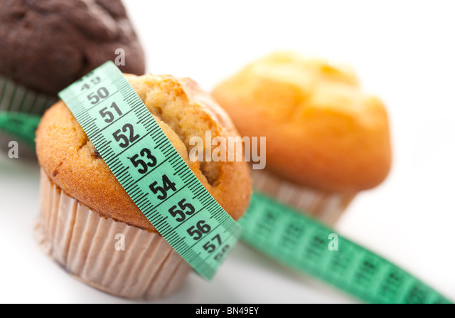 muffins with measuring tape on white background - Stock Image