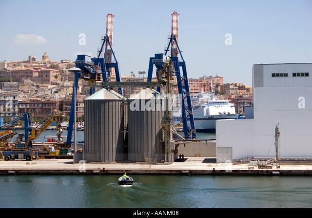 Cagliari Port Sardinia harbour harbor dock dockside crane boat ship cargo load loading unload unloading hold travel - Stock Image