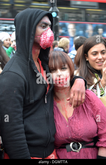 Couple dressed as zombies, Piccadilly Circus, London, England. For World Zombie Day charity event. - Stock Image