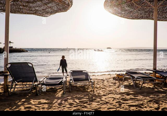 Young boy walking along beach, Hurgada, Red Sea, Egypt - Stock Image