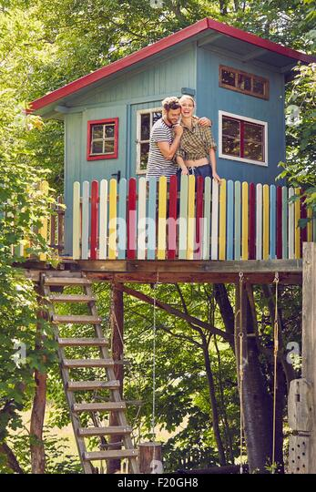 Young couple standing in tree house, hugging, laughing - Stock Image