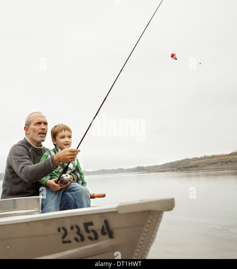 A day out at Ashokan lake A man showing a young boy how to fish sitting in a boat - Stock Image