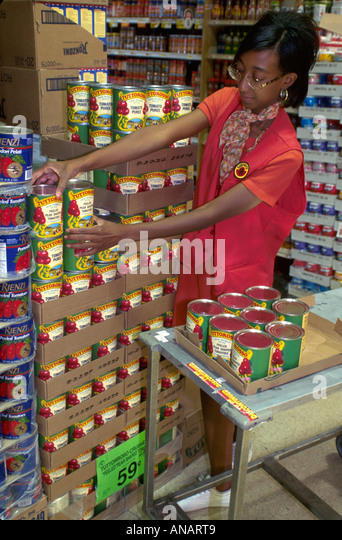 New Jersey Livingston Black woman grocery store clerk stacking canned food job ShopRite - Stock Image