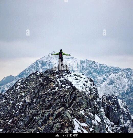Winter climber stands on Crib Goch facing Snowdon the highest mountain in Wales - Stock Image