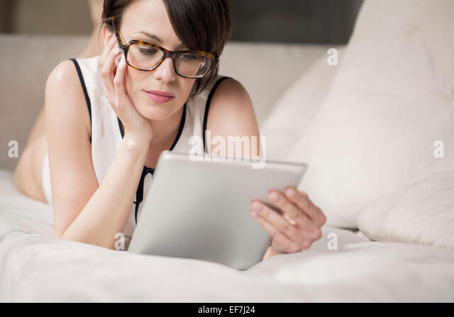 Woman lying on the bed and looking at a digital tablet - Stock-Bilder