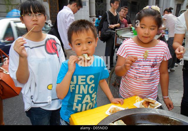 Shanghai China Huangpu District Dianchi Road Asian boy girl dumplings eating food street vendor - Stock Image
