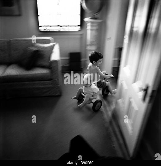 FL2671, NICK KELSH; Children tricycle riding through house - Stock-Bilder