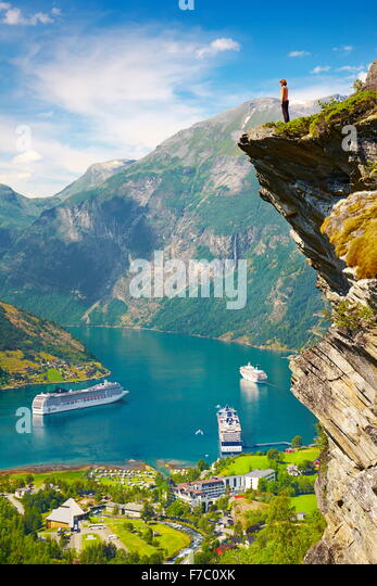Tourist standing on the rock cliff, cruise ships in the background, Geiranger Fjord, Norway - Stock-Bilder