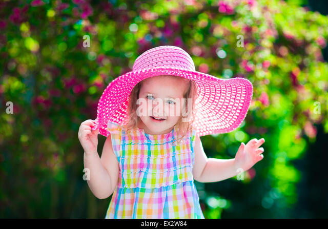 Little cute girl with flowers. Child wearing a pink hat playing in a blooming summer garden. Kids gardening. - Stock Image