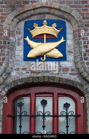 Symbol above a window at the Vismarkt (fish market) in the historic city of Bruges in Belgium. The historic city - Stock Image