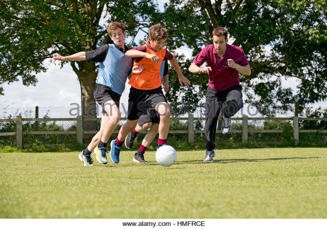 Middle schoolboys and teacher running playing soccer on field in physical education class - Stock-Bilder