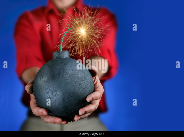 An old fashioned style round bomb with a lit fuse about to explode - Stock Image