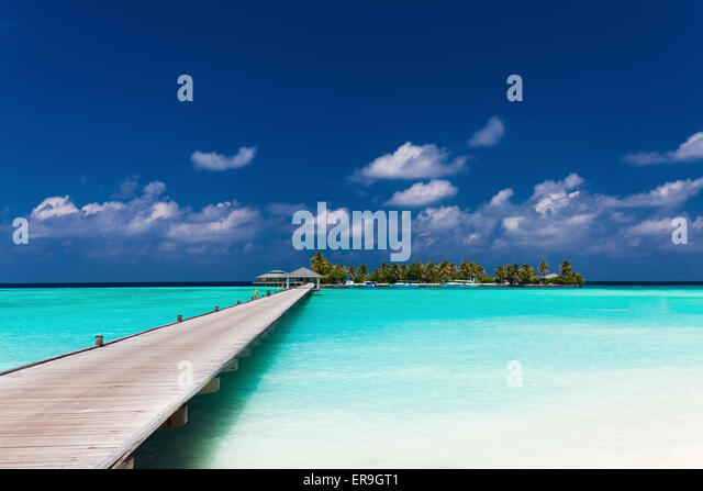 Wooden jetty to a tropical island over amazing lagoon in Maldives - Stock Image
