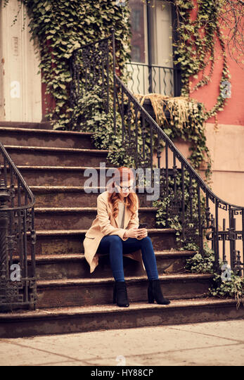 Young fashionable women sitting on steps on her smartphone in New York city - Stock Image