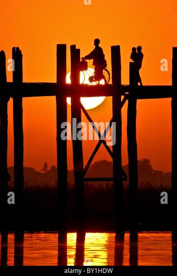 Myanmar, Burma, Amarapura, Taungthaman Lake, U Bein's Bridge.  A family walking home at sunset over U Bein's - Stock-Bilder