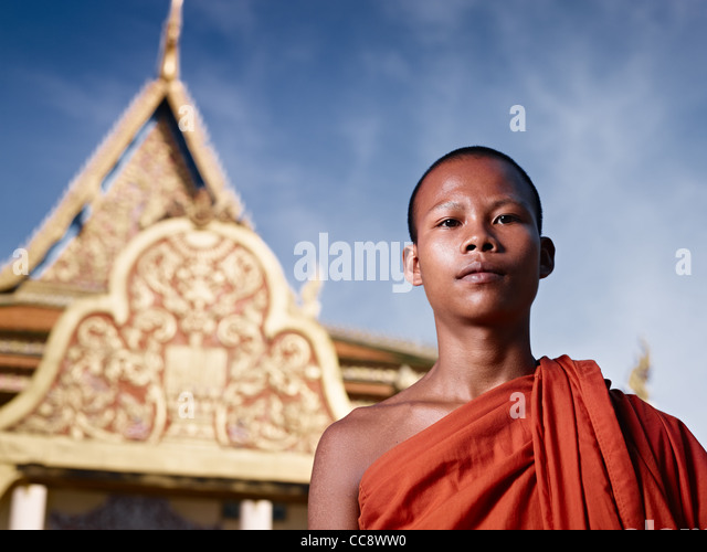 Young Asian monk smiling at camera in buddhist monastery, Phnom Penh, Cambodia, Asia. Low angle - Stock Image