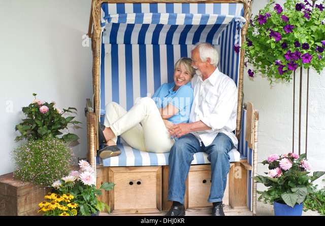 Retired couple relaxing on garden seat - Stock Image