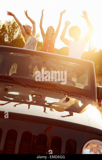 Three Women Dancing In Back Of Open Top Car - Stock Image