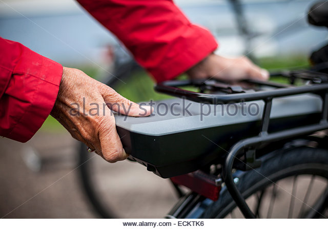Cropped image of senior woman inserting battery in backseat of electric bicycle - Stock Image