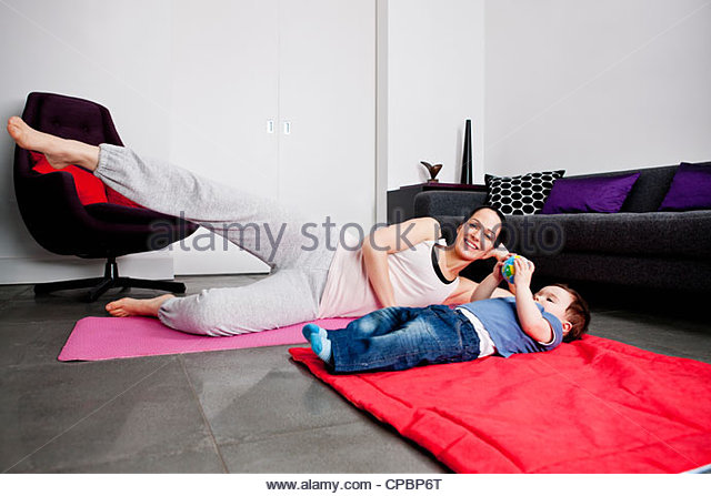 A mother and her baby son exercising at home - Stock-Bilder