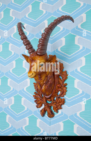 Plastic head of an ibex mounted on kitschy wallpaper from the 1960s or 1970s - Stock Image