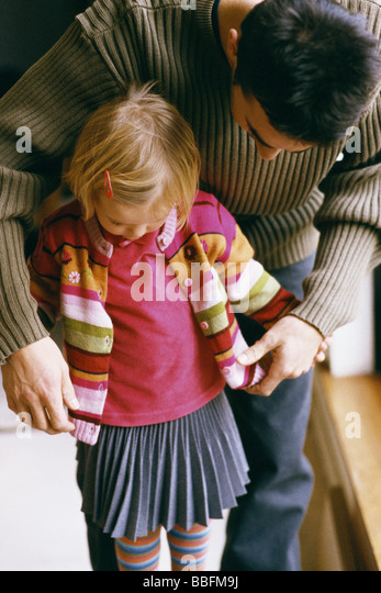 Father bending over to help young daughter button cardigan - Stock Image