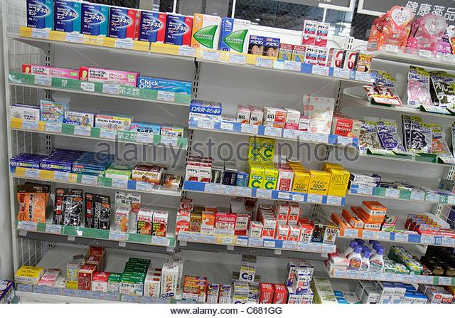 Japan Tokyo Shinjuku kanji hiragana katakana characters symbols Japanese English drugstore pharmacy shopping retail - Stock Image