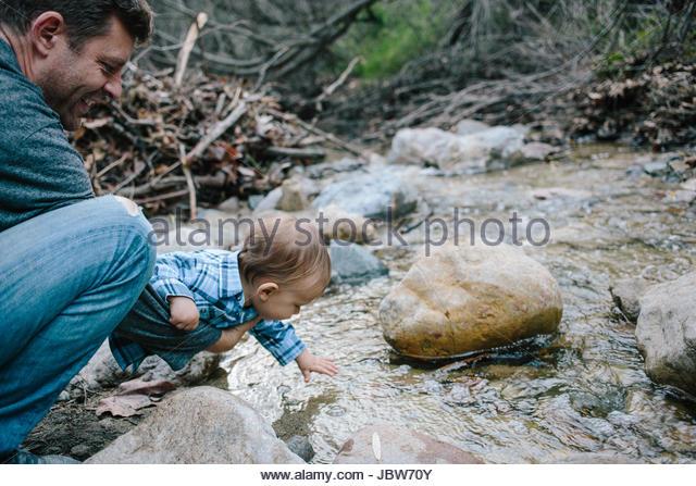 Father and baby boy investigating river, Venice Beach, Los Angeles, California, USA - Stock-Bilder