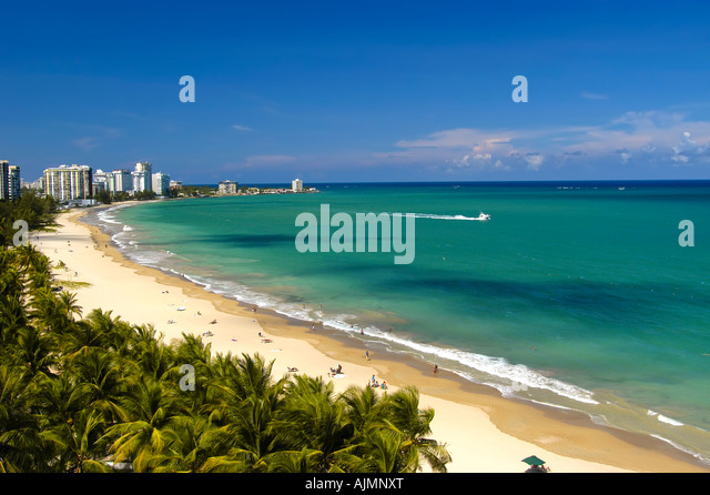 San Juan Puerto Rico Isla Verde beach with sunbathers, blue sky and resort hotels in background, plam trees lining - Stock Image
