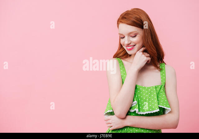 Portrait of young redhead woman wearing green dress and looking down - Stock Image