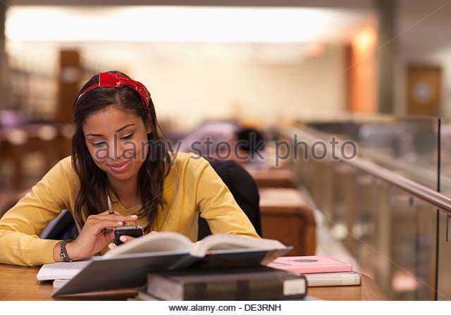 Student studying in library - Stock Image
