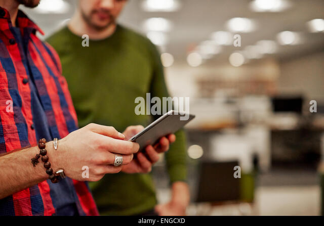 Two men looking at a digital tablet screen. - Stock Image