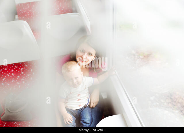 Mother with son in her lap traveling in train. - Stock-Bilder